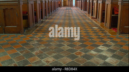 empty church pews with diamond pattern tiled floor - Stock Image