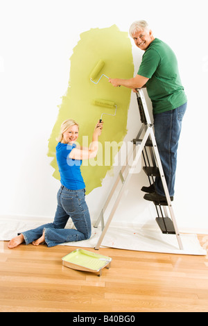 Middle aged couple painting wall green and looking at viewer - Stock Image