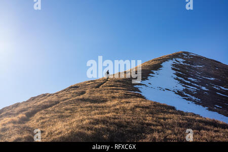 One Man hiker hiking alone climbing down a crest ridge of steep mountain path in winter. Taken from distance. - Stock Image