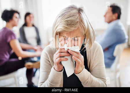 A portrait of senior depressed woman crying during group therapy. - Stock Image