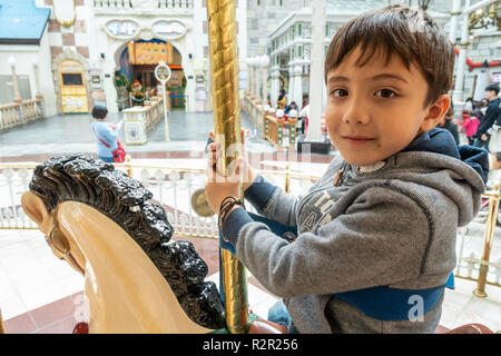 A happy young boy riding on a merry-go-round. - Stock Image