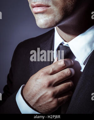 Closeup photo of a serious businessman wearing stylish black suit and tie over dark background, face part, mens - Stock Image
