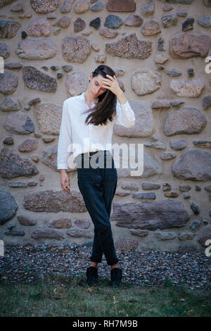 Portrait young man with long hair standing at stone wall - Stock Image