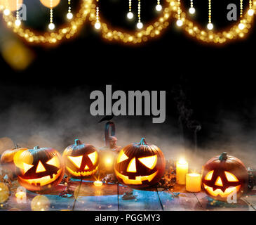 Spooky halloween pumpkins on wooden planks on black background. Celebration theme, copyspace for text. - Stock Image