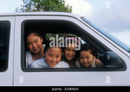 Portrait of 4 'Asian American' sisters with their heads out of car window - Stock Image