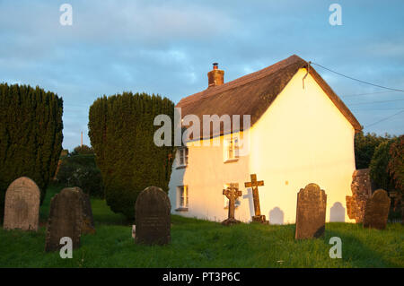 Thatched cottage beside a churchyard in Petrockstowe village, Devon, southwest England - Stock Image