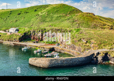 Boscastle Harbour, with its breakwater, boats and village houses. - Stock Image