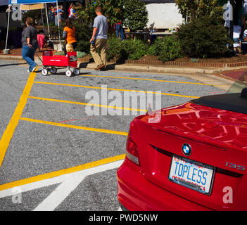 HICKORY, NC, USA-10/14/18: A red convertible with license tag reading 'topless', and an equally red wagon with young child. - Stock Image