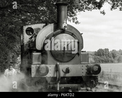 Monotone frontal shot of a steam locomotive at the Mid Suffolk Light Railway with engineer walking along side in the steam - Stock Image