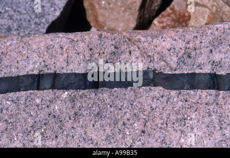 band banded boulder division geology grain layered rock seam stone texture divide bisect granite - Stock Image