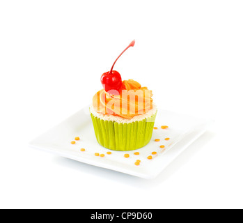 Vanilla cupcake with vanilla frosting topped with a maraschino cherry, on white background. - Stock Image