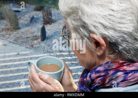 Senior old woman warming hands holding a warm drink looking out of the window on a cold snowy day in winter. UK, Britain - Stock Image