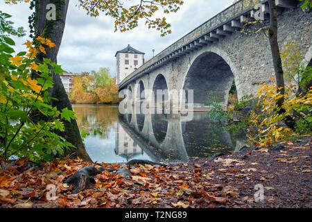 Limburg an der Lahn, Germany. View of Alte Lahnbrucke bridge reflecting in Lahn river in autum - Stock Image