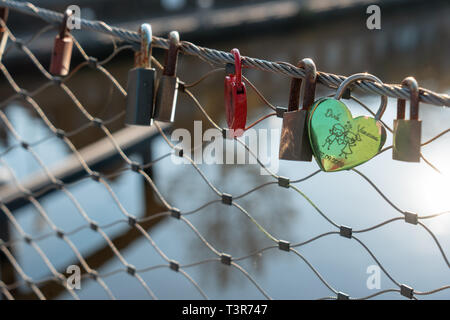 Love padlocks on railing of bridge with water in background in Holland - Stock Image