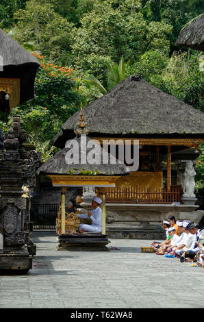 Prayer leader in a small cabin , Pura Tirta Empul temple, Ubud, Indonesia - Stock Image