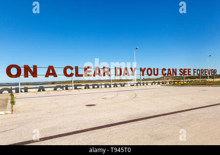 Large red rusty capital letters ON A CLEAR DAY YOU CAN SEE FOREVER blue sky background, Alqueva dam, Moura, Portugal - Stock Image