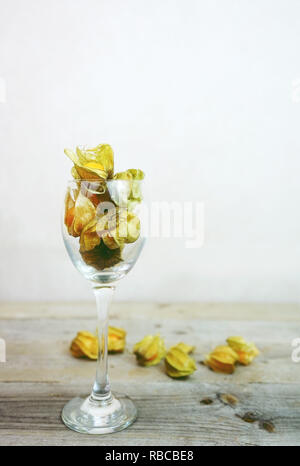 Beautiful and elegant macro close-up of a lot orange tasty fruit named physalis from Peru, South America, in a crystal glass with space over wooden ta - Stock Image