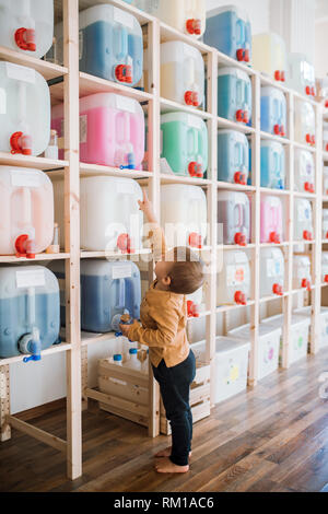 A small toddler boy standing by dispensers in zero waste shop. - Stock Image