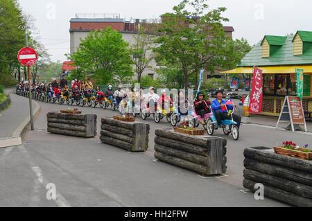 Group of Taiwanese tourists on trikes coupled together like a conga line. Onuma, Hokkaido, Japan. - Stock Image