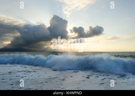 Sunset ocean is a serene scenic seascape on the beach with the bright sun setting on the ocean horizon as water - Stock Image