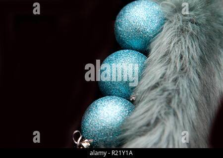Three blue holiday ornaments in a horizontal row on black copy space - Stock Image
