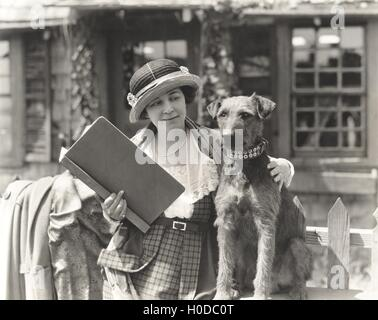 Woman posing with her wire hair terrier - Stock Image