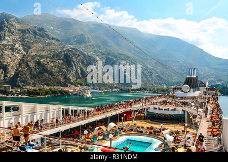 Cruise passengers enjoy the pool and deck on their cruise ship as they sail away from the coastal city of Kotor, Montenegro, on the Adriatic coast. - Stock Image