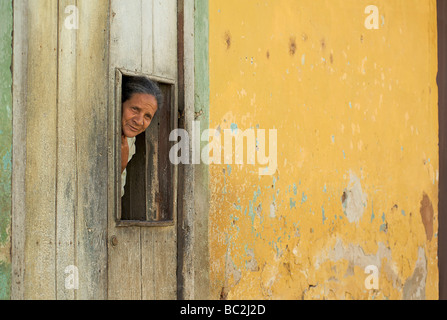 Cuban woman peering from a hatch in the door to her brightly painted colonial home. Trinidad, Cuba - Stock Image