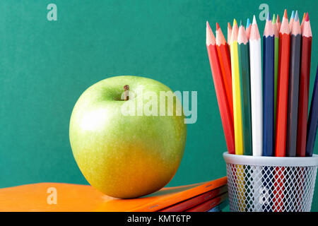 Image of crayons and green apple against blackboard - Stock Image
