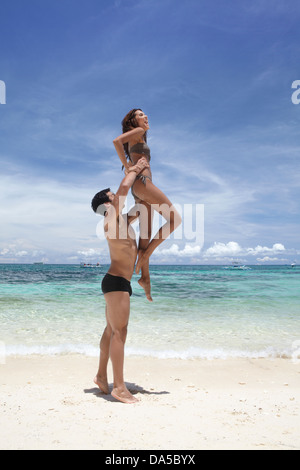 A couple playing on a beach. - Stock Image
