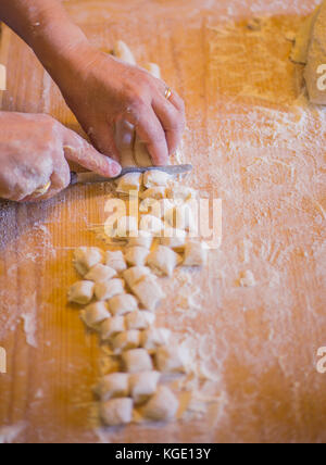Handmade processing of dumplings above a wooden board. - Stock Image