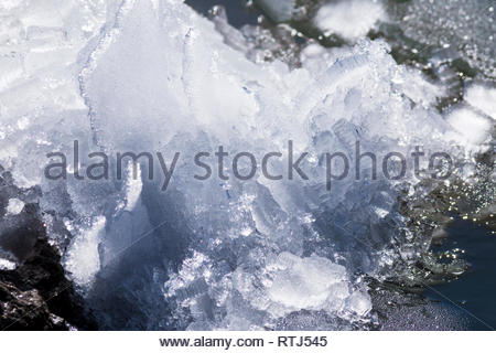 Ice pushed up on rock by wind, perhaps 8 inches high - Stock Image
