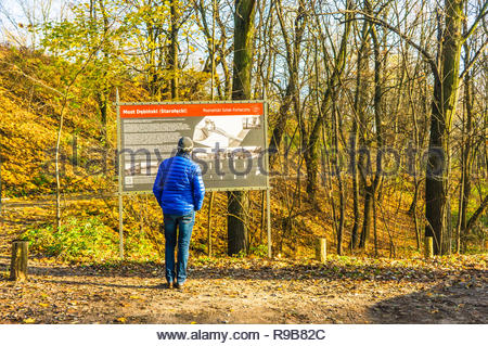 Poznan, Poland - November 17, 2018: Man looking at a information sign in the Debinski forest on a sunny day.  - Stock Image