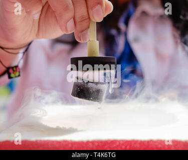 Demonstration of Quantum Magnetic Levitation and Suspension Effect. A splash of liquid nitrogen cools a ceramic superconductor forcing it to float in  - Stock Image