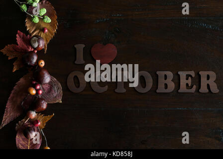 beautiful rustic fall flat lay with leaves, berries, chestnuts and letters I love october on wooden background - Stock Image