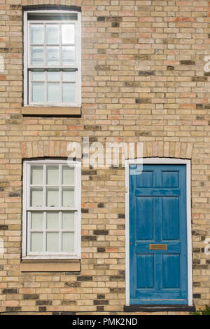 Blue pastel vintage front door on a restored brick wall of a Georgian house residential building with white wooden sash windows - Stock Image