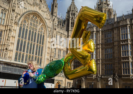 A woman protestor holds some balloons with the letters E and U during a pro-EU brexit protest opposite Parliament, on 11th March 2019, in Westminster, London, England. - Stock Image