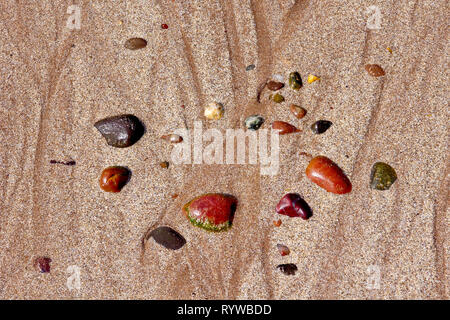 A collection of colourful scattered pebbles left behind on the sand after the tide goes out. - Stock Image