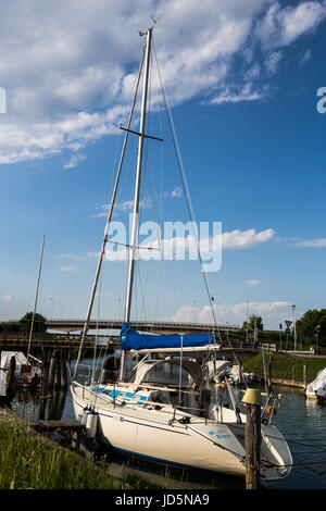 Sailboat moored at the dock in Caorle - Italy in a beautiful sunny day - Stock Image