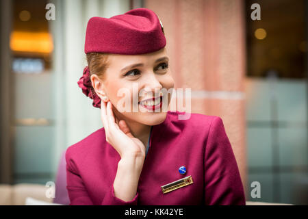Young attractive female working as cabin crew for Qatar Airways on London layover. Pretty smile, looking happy and - Stock Image