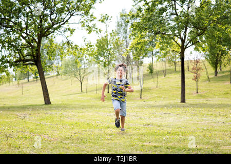 Energetic young boy running across the grass in a spring park racing towards the camera at speed between the trees - Stock Image