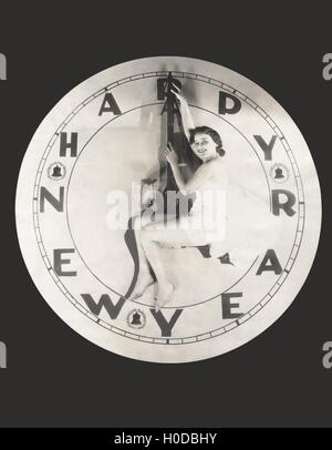 Woman sitting on huge Happy New Year clock - Stock Image