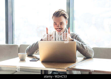 Handsome satisfied positive young freelancer in grey blazer are sitting in cafe, watching on laptop with toothy smile and showing thumbs up. indoor, f - Stock Image