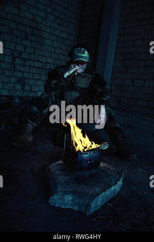 Special forces soldier smoking a cigarette while sitting by the fire in a ruined building. - Stock Image