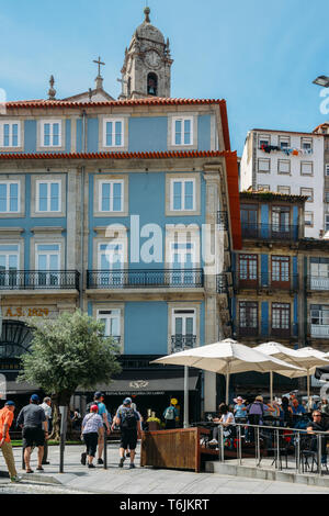 Porto, Portugal - April 29, 2019: People sit at cafe terraces on a sunny afternoon in the historic centre of Porto - UNESCO World Heritage Site - Stock Image
