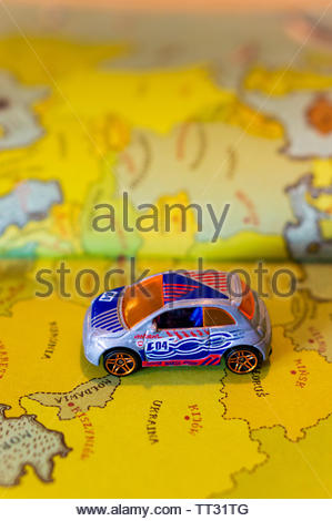 Mattel Hot Wheels Fiat 500 car on a page with European map from a opened atlas book on circa June 2019 in Poznan, Poland. - Stock Image