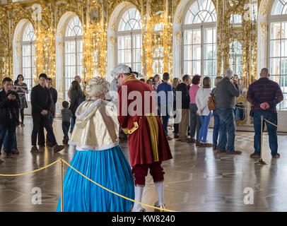 Tourists inside an interior state room with ornate decorative golden features, Catherine Palace (Tsarskoe Selo), - Stock Image