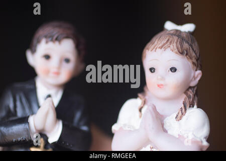 Cake topper Catholic holy communion ceremony religious boy and girl praying to Christian God in church. - Stock Image