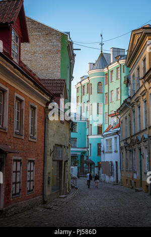 Tallinn street, view of a young couple walking along a colorful street in the Old Town quarter of Tallinn on a summer evening, Estonia. - Stock Image
