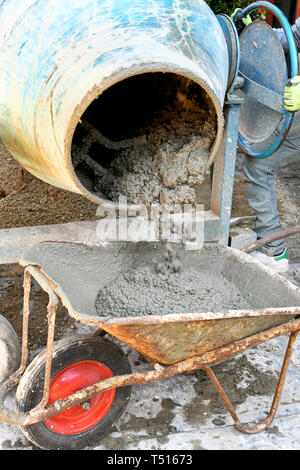 The technician worker loading cement into wheelbarrow pouring it out of electric concrete mixer for construction works - Stock Image